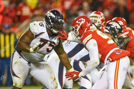 Denver Broncos offensive tackle Menelik Watson (75) and Kansas City Chiefs linebacker Tanoh Kpassagnon (92) do battle at the line of scrimmage during the NFL Football Game between the Denver Broncos and the Kansas City Chiefs at Arrowhead Stadium in Kansas City, Missouri