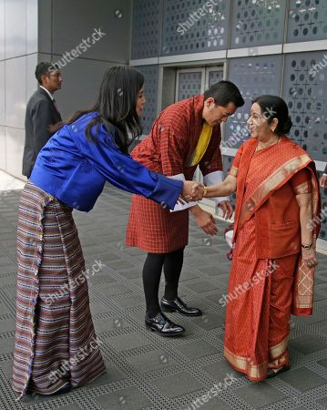 Indian External Affairs Minister Sushma Swaraj, right, shakes hands with Bhutan's Queen Jetsun Pema, left as King Jigme Khesar Namgyal Wangchuck, and their son prince Jigme Namgyel Wangchuck stand behind after receiving them at the airport in New Delhi, India, . The Bhutan royals arrived Tuesday on a four-days visit to India