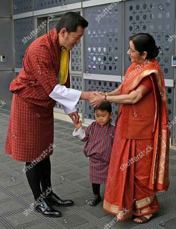 Stock Picture of Sushma Swaraj, Jigme Khesar Namgyal Wangchuck, Jigme Namgyel Wangchuck. Indian External Affairs Minister Sushma Swaraj, right, shakes hands with Bhutan's King Jigme Khesar Namgyal Wangchuck, as his son prince Jigme Namgyel Wangchuck stands beside as she receives them at the airport in New Delhi, India, . The Bhutan royals arrived Tuesday on a four-days visit to India