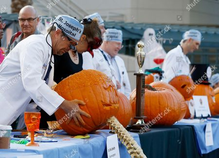 Stock Image of Dr. Kris Smith, left, of Dignity Health St. Joseph's Hospital and Medical Center, displays his carved out a pumpkin as he joins other surgeons during the Doc-O-Lantern Pumpkin Carving Contest, in Phoenix