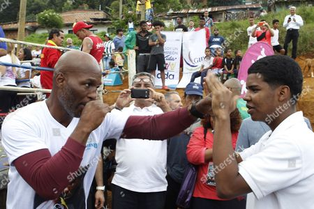 Former world champion Bernard Hopkins (L) teaches a youngster how to box in the neighborhood La Honda, in Medellin, Antioquia, Colombia, 31 October 2017.  Former world champions Bernard Hopkins and Oscar de la Hoya and other boxers visited a La Honda neighborhood where they brought hope by sharing their life histories and teaching some of their secrets in the ring during the 96th Annual Boxing Convention of the World Boxing Association (WBA).