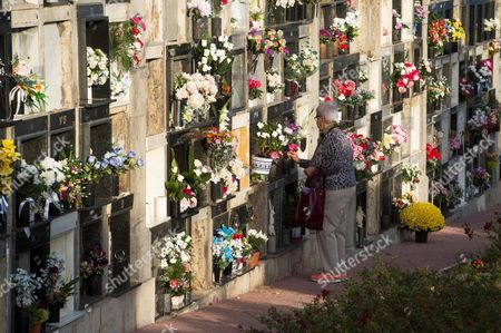 A woman places flowers at the grave of a loved one at the cementery of Ballena on the All Saints Day in Castro Urdiales, Cantabria, Spain, 01 November 2017. All Saints' Day is a Christian festival mainly celebrated by Catholics to remember the dead. People visits the graves of loved ones and place candles and flowers.