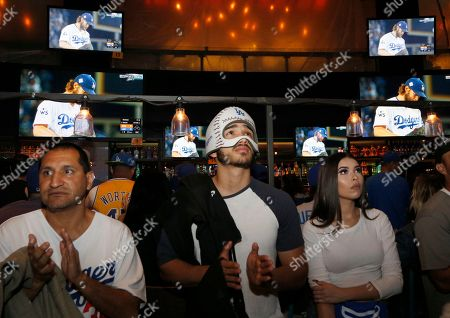 Marco Mendoza, of San Bernardino, Calif., center, watches the action at Tom's Urban restaurant and bar in the L.A. Live entertainment complex in downtown Los Angeles during decisive Game 7 of the World Series between the Los Angeles Dodgers and the Houston Astros . The Asatros won, 5-1