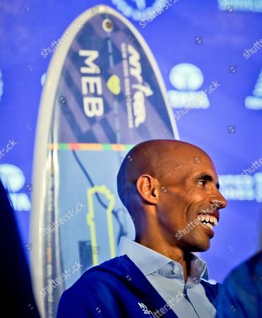 Marathoner Meb Keflezighi stands next to a surfboard presented to him during a press conference for the 2017 TCS New York City Marathon, in New York. Keflezighi, the face of American long-distance running, wraps up his marathon career where it began in 2002 on the multicultural streets of New York