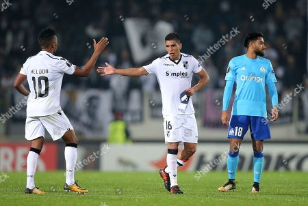 Vitoria's Paolo Hurtado, center, and Heldon celebrate at the end of the Europa League group I soccer match between Vitoria SC and Olympique de Marseille at the D. Afonso Henriques stadium in Guimaraes, Portugal, . Hurtado scored the only goal of the game