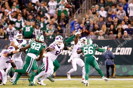 Buffalo Bills quarterback Tyrod Taylor, second from right, is hit by New York Jets defensive end Muhammad Wilkerson, center back, as he throws a pass during the second half of an NFL football game, in East Rutherford, N.J