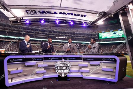 The cast of Thursday Night Football, from left, Rich Eisen, Marshall Faulk, LaDainian Tomlinson and Michael Irvin talk during their postgame show after to an NFL football game between the New York Jets and the Buffalo Bills, in East Rutherford, N.J