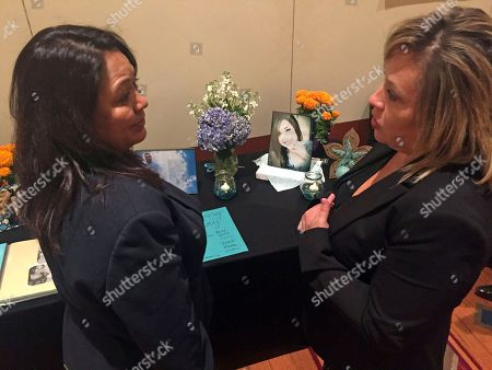 Doreen Wonda, Paula Ortiz. State Rep. Doreen Wonda Johnson, left, of Church Rock, N.M., pauses to console Paula Ortiz, of Chimayo, whose daughter, pictured on the table, died of a heroin overdose in 2016, in Santa Fe, N.M.. A Day of the Dead altar with family photos the departed stood in silent testimony to New Mexico's struggle to reduce the toll of opioid addiction, as state lawmakers and public health experts searched at a policy summit in Santa Fe, N.M., for new weapons against fatalities