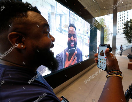 Apple employee Kenny Johnson tries out one of 12 Animojis that can mirror 50 different muscle movements in the Apple iPhone X at the new Apple Michigan Avenue store along the Chicago River, in Chicago