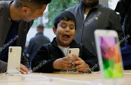 Aadhyan Vaka, 6, of Plainsboro, N.J., reacts while playing with the animoji feature of the new iPhone X at the Apple Union Square store, in San Francisco