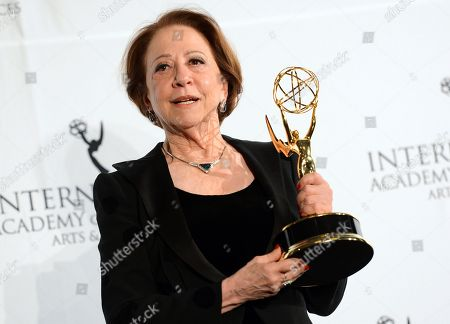 """Brazilian actress Fernanda Montenegro poses with her """"Best Performance by an Actress"""" award for her role in """"Sweet Mother"""" at the 2013 International Emmy Awards Gala in New York. Montenegro is nominated again for her role in the comedy series. The awards will be presented Nov. 23 at a gala in New York"""