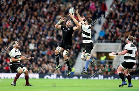 Luke Romano of The New Zealand All Blacks & Sam Carter of The Barbarians compete for a high ball