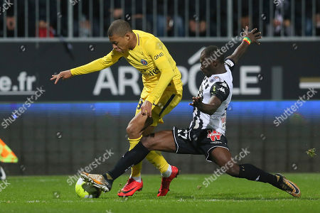 Paris Saint Germain's Kylian Mbappe, left, is tackled by Angers' defender Saliou Ciss during their French League One soccer match, in Angers, western France. Paris won 5-0