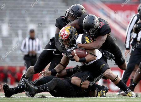Maryland running back Lorenzo Harrison III, center left, is hit by Rutgers defensive back Damon Hayes, top right, linebacker Deonte Roberts, top left, and linebacker Trevor Morris, bottom, during the first half of an NCAA college football game, in Piscataway, N.J
