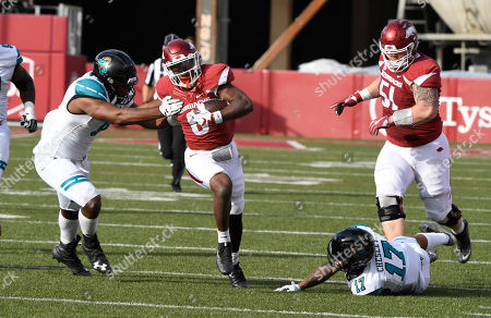 Arkansas running back T.J. Hammonds shakes Costal Carolina defenders Shane Johnson (9) and Anthony Chelsey (17) as he runs for a touchdown during the first half of an NCAA college football game, in Fayetteville, Ark