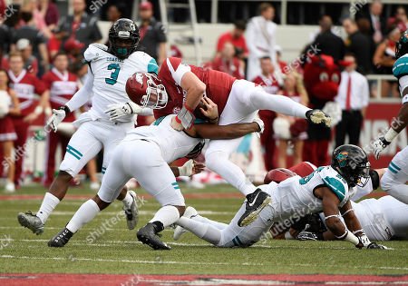 Arkansas quarterback Cole Kelley is tackled by Costal Carolina defender Shane Johnson during the first half of an NCAA college football game, in Fayetteville, Ark