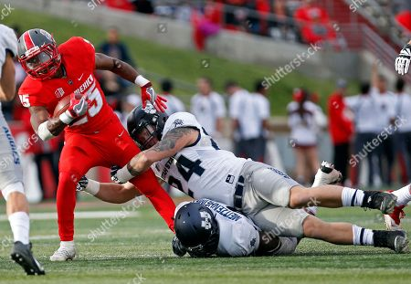 Stock Picture of Tyrone Owens, Dalton Baker, Kevin Meitzenheimer. New Mexico running back Tyrone Owens (25) is stopped by Utah State linebacker Dalton Baker (24) and linebacker Kevin Meitzenheimer during the first half of an NCAA college football game in Albuquerque, N.M