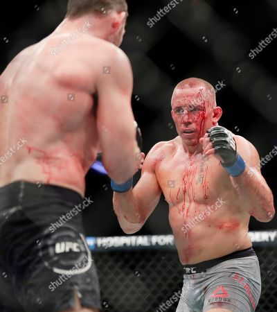 Michael Bisping, Georges St-Pierre. Georges St-Pierre, right, of Canada, faces England's Michael Bisping, during a middleweight title mixed martial arts bout at UFC 217 early, in New York. St-Pierre won the fight