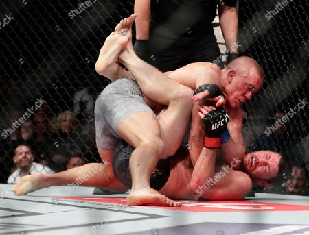 Michael Bisping, Georges St-Pierre. Georges St-Pierre, above, of Canada, fights England's Michael Bisping during a middleweight title mixed martial arts bout at UFC 217, in New York. St-Pierre won the fight