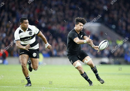 Ardie Savea of New Zealand passes the ball with brother Julian Savea of the Barbarians behind him