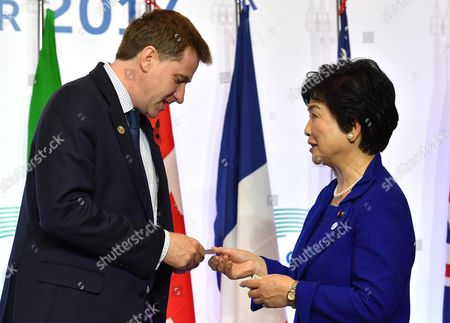 Britain's Undersecretary for Public Health and Community Health Steve Brine (L) and Japan's State Minister, Michiyo Takagi (R) exchange business cards during the G7 Health Ministerial Meeting in Milan, Italy, 05 November 2017.