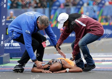 People come to help Meb Keflezighi of the United States after he collapsed at the finish line of the New York City Marathon in New York