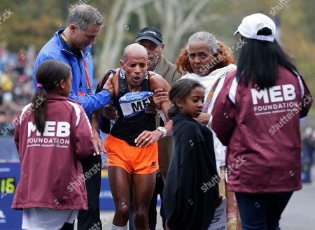 People come to help Meb Keflezighi of the United States, third from left, after collapsed at the finish line of the New York City Marathon in New York
