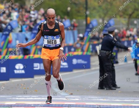 Meb Keflezighi of the United States stumbles as he crosses the finish line of the New York City Marathon in New York