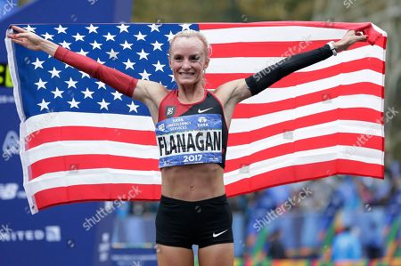 Shalane Flanagan of the United States poses for pictures after crossing the finish line first in the women's division of the New York City Marathon in New York