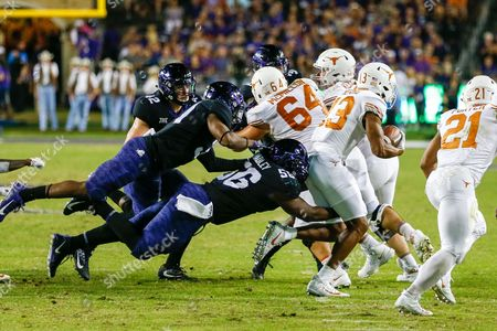 Texas Christian University DT Chris Bradley (56) dives to tackles University of Texas WR Jerrod Heard (13) during the game between The University of Texas and Texas Christian University at Amon G. Carter Stadium in Fort Worth, Texas