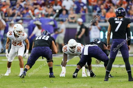 University of Texas DL Charles Omenihu (90) and University of Texas DB John Bonney (24) line up aginst the TCU offesnive line during the game between The University of Texas and Texas Christian University at Amon G. Carter Stadium in Fort Worth, Texas