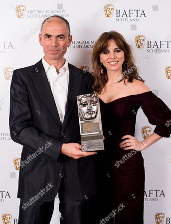 Stock Picture of John Hodge accepting on the behalf of Ewen Bremner - Actor Film - T2 Trainspotting with citation reader Ophelia Lovibond