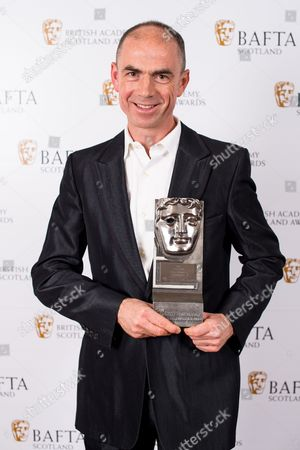 Stock Image of John Hodge accepting on the behalf of Ewen Bremner - Actor Film - T2 Trainspotting