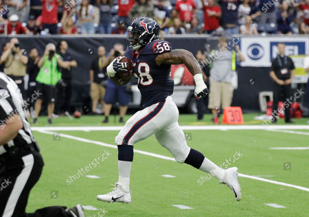 Houston Texans linebacker Lamarr Houston (58) returns a fumble recovery for a touchdown against the Indianapolis Colts during the first half of an NFL football game, in Houston