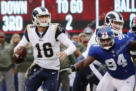 Los Angeles Rams' Jared Goff (16) looks to pass during the first half of an NFL football game as New York Giants' Dalvin Tomlinson (94) closes in, in East Rutherford, N.J. Goff threw a pass for a touchdown to Tyler Higbee on the play