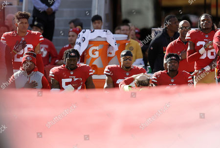 Eli Harold, Eric Reid, Marquise Goodwin. San Francisco 49ers outside linebacker Eli Harold, from second from left, safety Eric Reid and wide receiver Marquise Goodwin kneel during the national anthem before an NFL football game against the Arizona Cardinals in Santa Clara, Calif