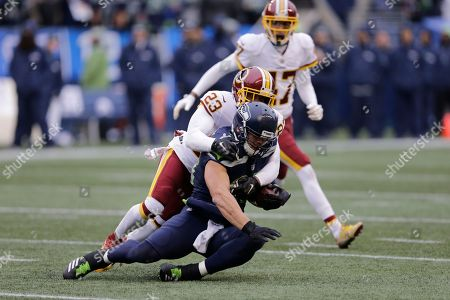 Washington Redskins free safety DeAngelo Hall (23) tackles Seattle Seahawks tight end Jimmy Graham (88) in the second half of an NFL football game, in Seattle