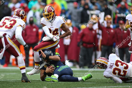 Seattle Seahawks quarterback Russel Wilson (3) runs to try and pick up the first down and his pushed into Washington Redskins cornerback Josh Norman (24) by Washington Redskins safety DeAngelo Hall (23) during a game between the Washington Redskins and the Seattle Seahawks at CenturyLink Field in Seattle, WA on , 2017