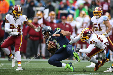Seattle Seahawks quarterback Russel Wilson (3) runs to try and pick up the first down and his pushed down by Washington Redskins safety DeAngelo Hall (23) during a game between the Washington Redskins and the Seattle Seahawks at CenturyLink Field in Seattle, WA on , 2017