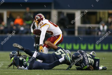 Washington Redskins wide receiver Brian Quick (83) is hit by Seattle Seahawks safety Kam Chancellor (31), Seattle Seahawks linebacker Bobby Wagner (54) and Seattle Seahawks cornerback Richard Sherman (25) csm