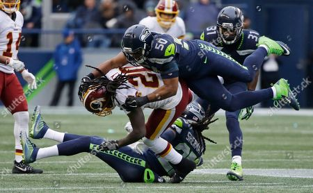 Washington Redskins running back Rob Kelley is brought down by Seattle Seahawks outside linebacker K.J. Wright (50) and cornerback Richard Sherman (25) as strong safety Kam Chancellor (31) looks on in the second half of an NFL football game, in Seattle