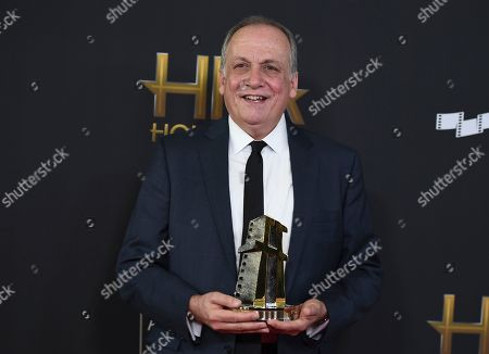 """Joe Letteri poses with the """"Hollywood visual effects award"""" for """"War for the Planet of the Apes"""" at the Hollywood Film Awards at the Beverly Hilton hotel, in Beverly Hills, Calif"""