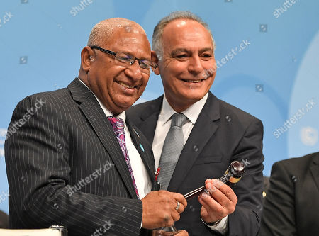 President of COP 22 Salaheddine Mezouar from Morocco, right, hands over a gavel to Fiji's prime minister and president of COP 23 Frank Bainimarama, left, during the opening of the UN Climate Change Conference in Bonn, Germany