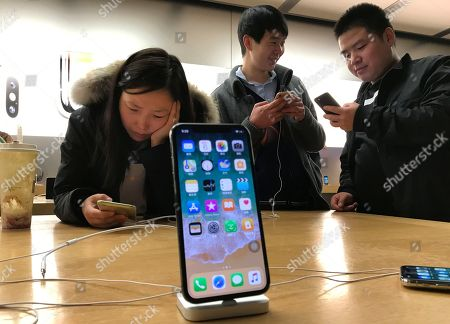 Shoppers check out the iPhone X at an Apple store in Beijing, China, . Apple's iPhone X went on sale as the company scrambles to meet demand for a marquee device that sports a lush screen, facial-recognition skills and a $1,000 price tag