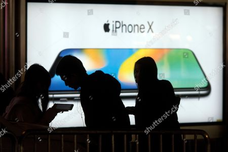 Youths use their mobile phones near an advertisement for iPhone X in Beijing, China, . Apple's iPhone X went on sale as the company scrambles to meet demand for a marquee device that sports a lush screen, facial-recognition skills and a $1,000 price tag