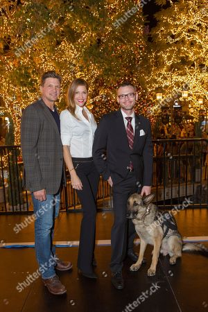 """Marc Blucas, from left, Tricia Helfer, Captain Jason Haag and service dog Axel attend a screening for Hallmark Movies & Mysteries """"Operation Christmas"""" at The Gove on in Los Angeles"""