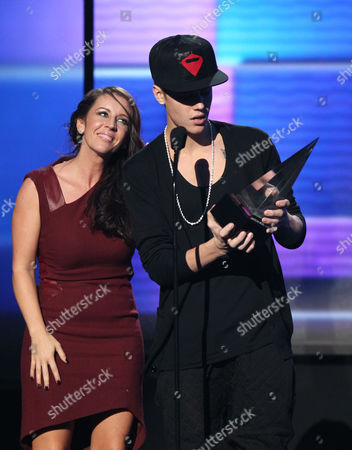 Justin Bieber, right, accepts the award for artist of the year as he is joined by his mom Pattie Malette on stage at the 40th Anniversary American Music Awards, in Los Angeles