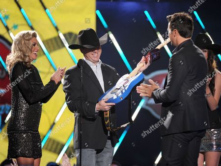 Stock Image of From left, Shada Brazile and Trevor Brazile present the male artist of the year award to Luke Bryan onstage at the American Country Awards at the Mandalay Bay Resort & Casino, in Las Vegas, Nev