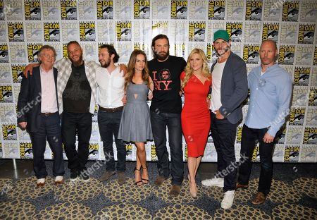 """From left, Writer and producer Michael Hirst Actors Travis Fimmel, George Blagden, Jessalyn Gilsig, Clive Standen, Katheryn Winnick, Gustaf Skarsgard and History Senior Vice President of Development and Programming Dirk Hoogstra attends the """"Vikings"""" panel on Day 3 of Comic-Con International on in San Diego, Calif"""