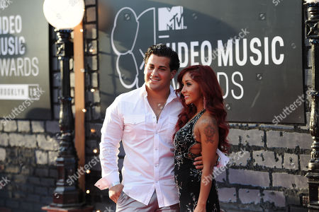 """Jionni LaValle, left, and Nicole """"Snooki"""" Polizzi arrive at the MTV Video Music Awards, at the Barclays Center in the Brooklyn borough of New York"""